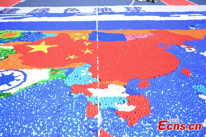 Students create world map with 300,000 bottle caps